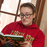 Photo of student reading textbook